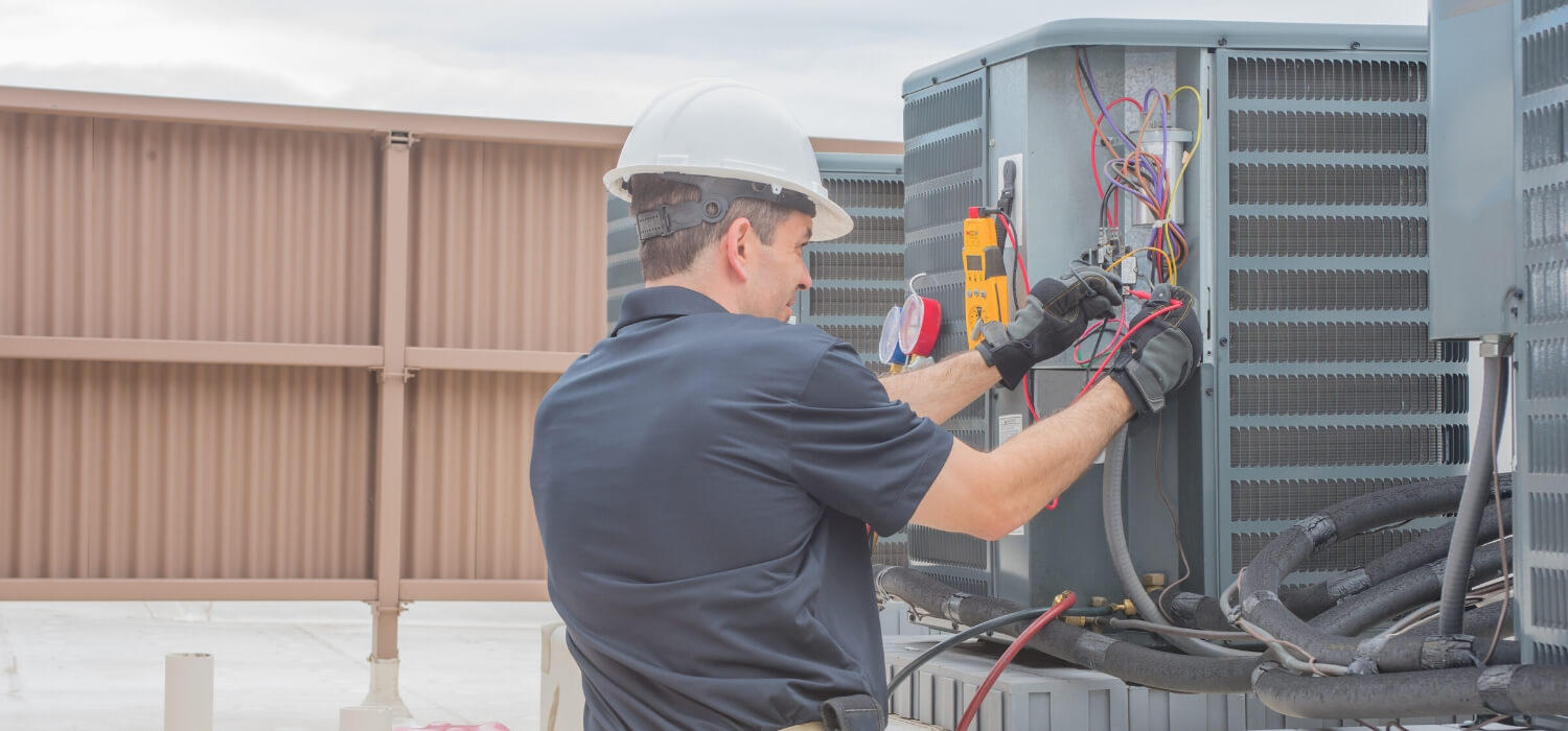 technician working on noisy air conditioner