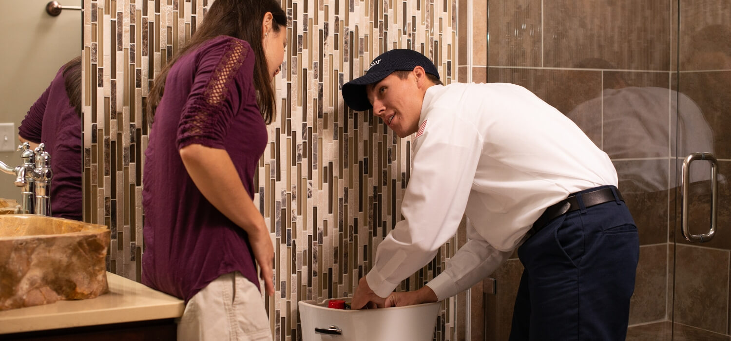 technician showing customer parts of a toilet
