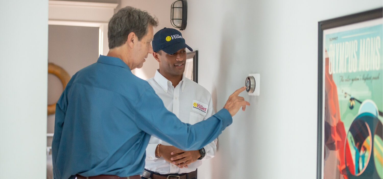 technician performing ac maintenance on thermostat