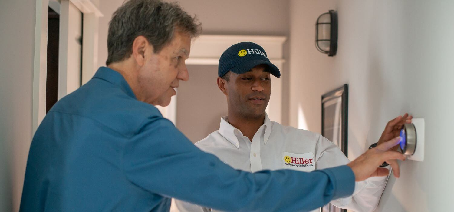 technician helping customer with learning thermostat
