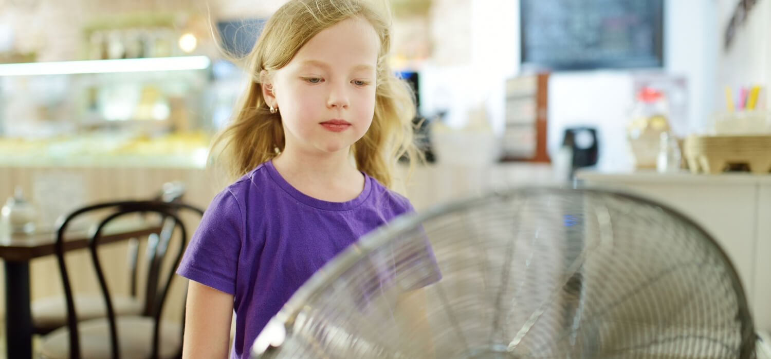 little girl in front of oscillating fan in kitchen dealing with common air conditioning problems