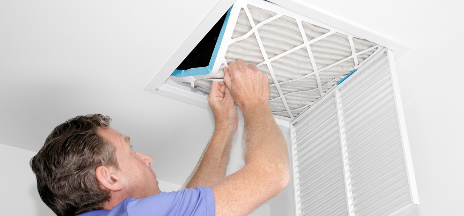homeowner removing common air conditioning problem dirty air filter