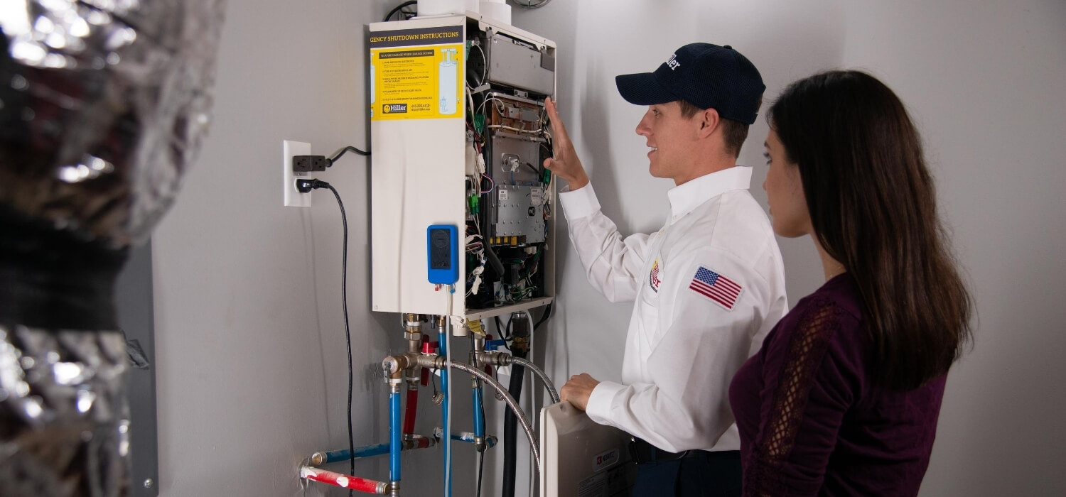 technician performing plumbing maintenance check on tankless water heater