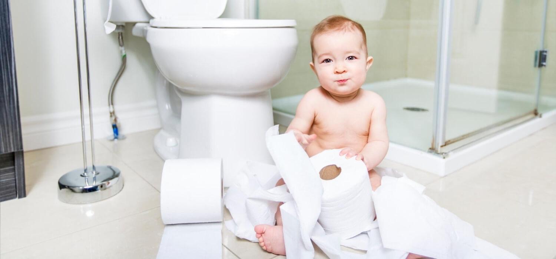 baby with toilet paper in bathroom floor