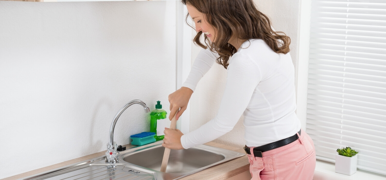 woman using plunger to unclog kitchen sink