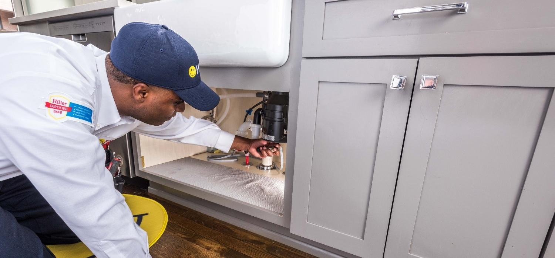 technician working on jammed garbage disposal under kitchen sink