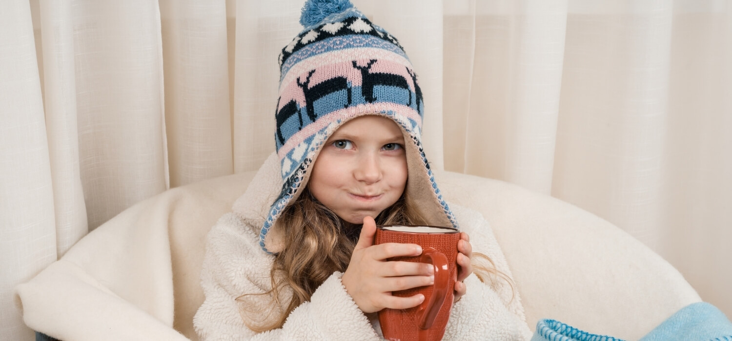 Child Sitting Inside With Hot Drink and Winter Clothes