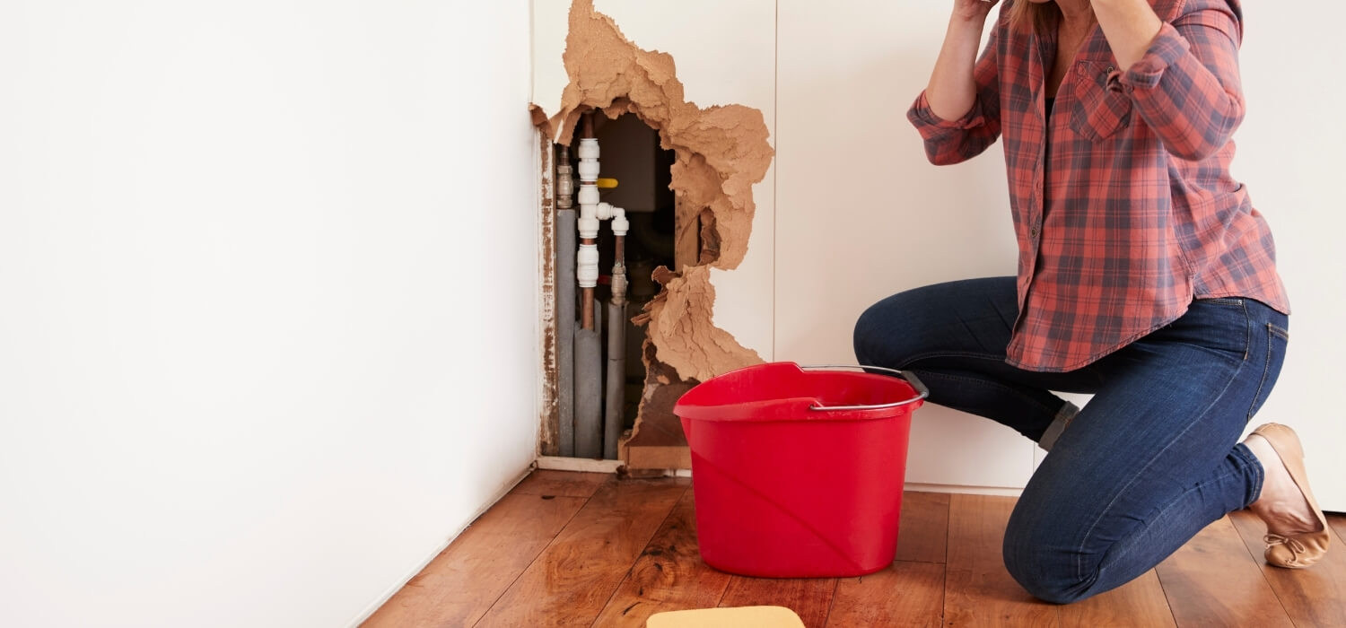 Homeowner Cleaning up from a Busted Pipe and Calling a Plumber