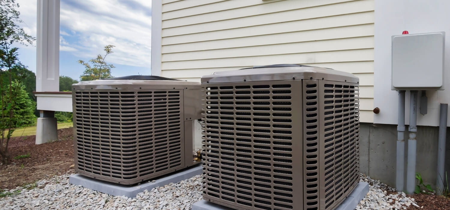 Two HVAC Units Outside on Gravel
