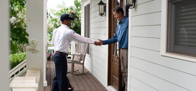 HVAC Technician Greeting Customer at Front Door
