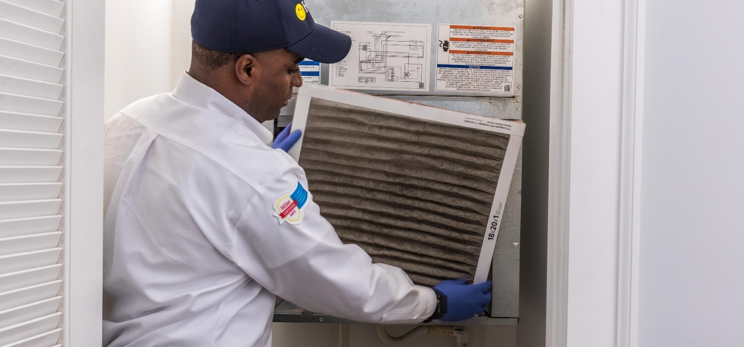 HVAC Technician Providing AC Maintenance by Changing the Air Filter