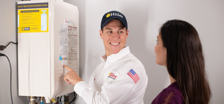 Hiller Plumber Showing Customer Tankless Water Heater
