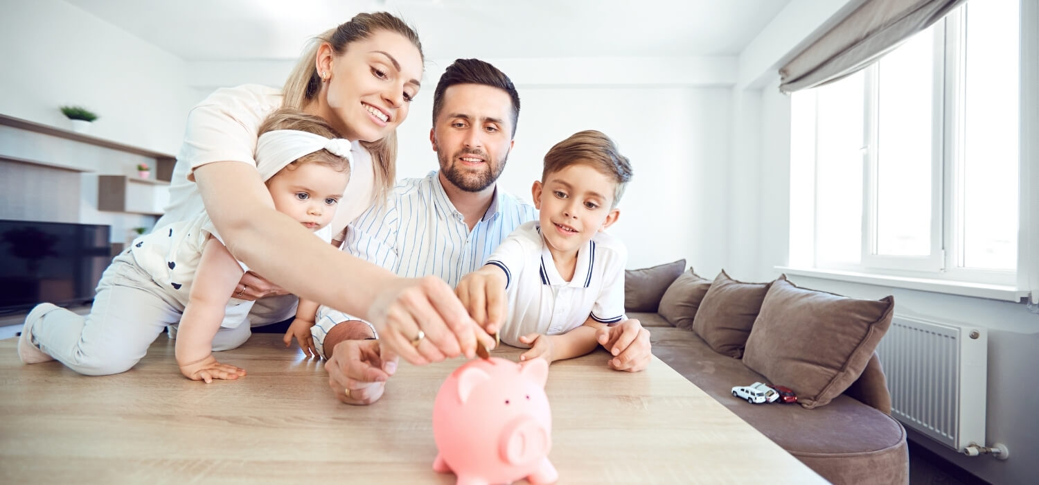 Family Inserting Coins into Piggy Bank