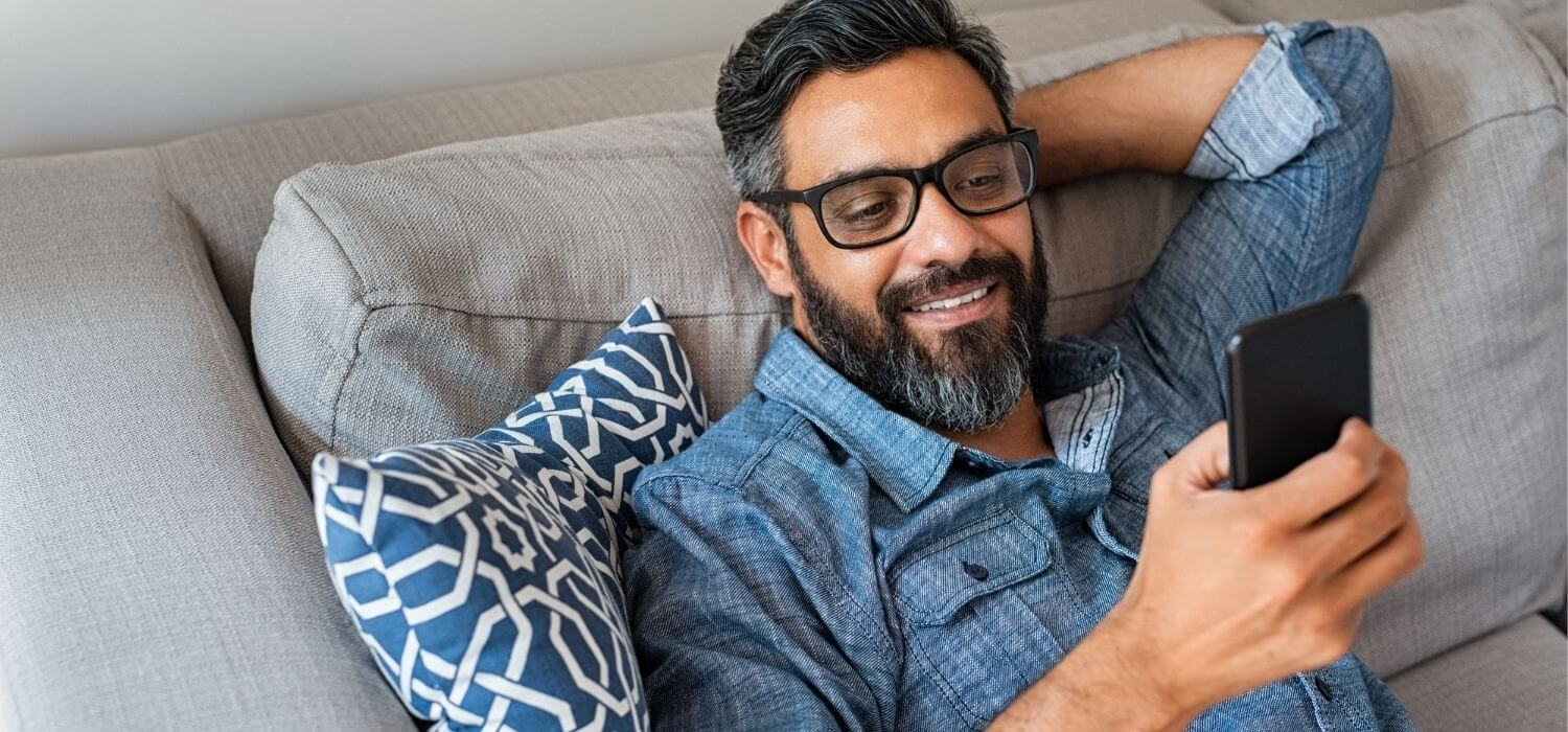 Homeowner on Couch Using Smart Home Devices