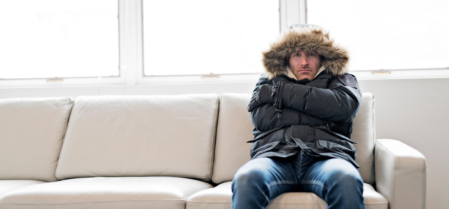 Homeowner in Coat on the Couch Needing a Furnace Repair from an HVAC Service Company