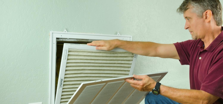 Homeowner Replacing Air Filter
