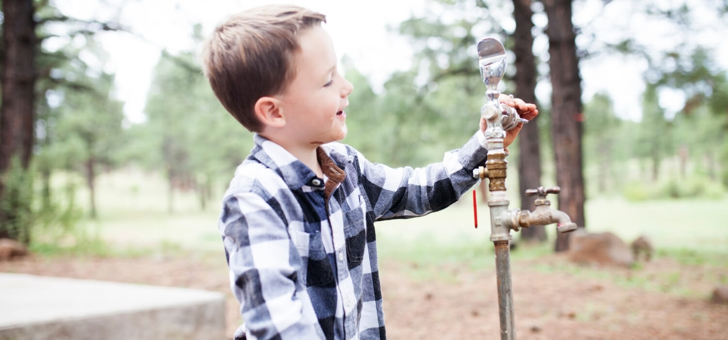 Boy at Water Spigot with No Water