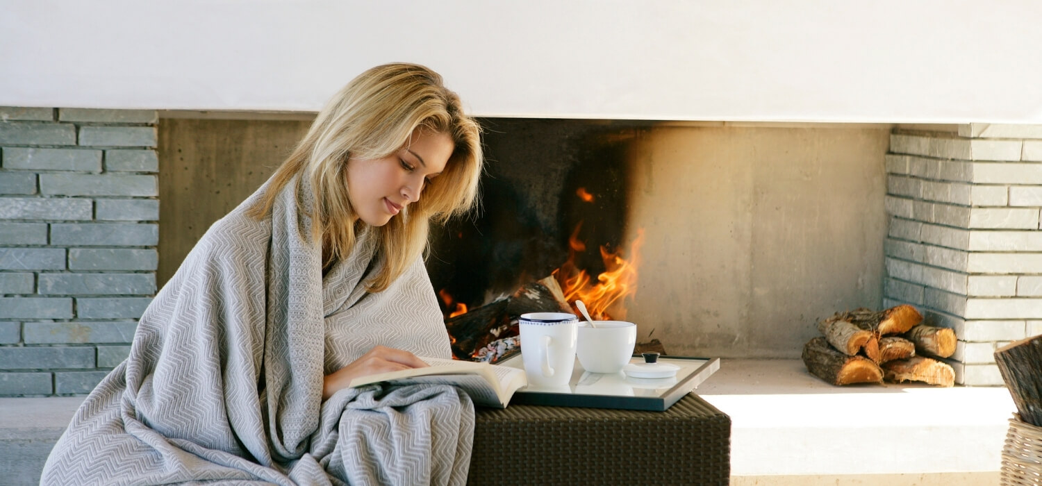 Lady Cold Reading a Book Inside With a Blanket by the Fire