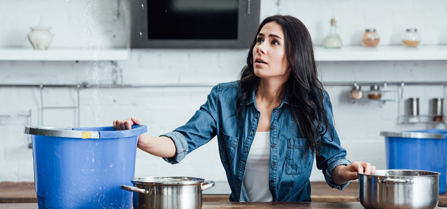 Woman Catching Dripping Water in a Bucket on the Counter